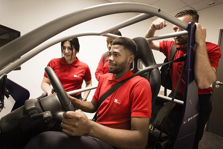 Un étudiant de l'épide est en pleine séance à bord d'un simulateur automobile entouré de 3 de ses camarades.