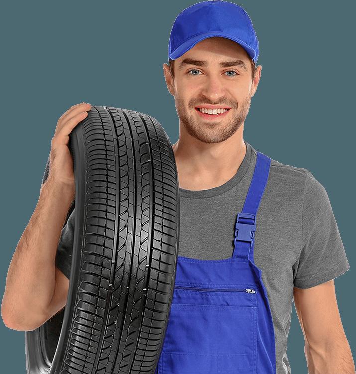 Photographie d'un pneumaticien souriant en bleu de travail avec un pneu neuf à l'épaule.