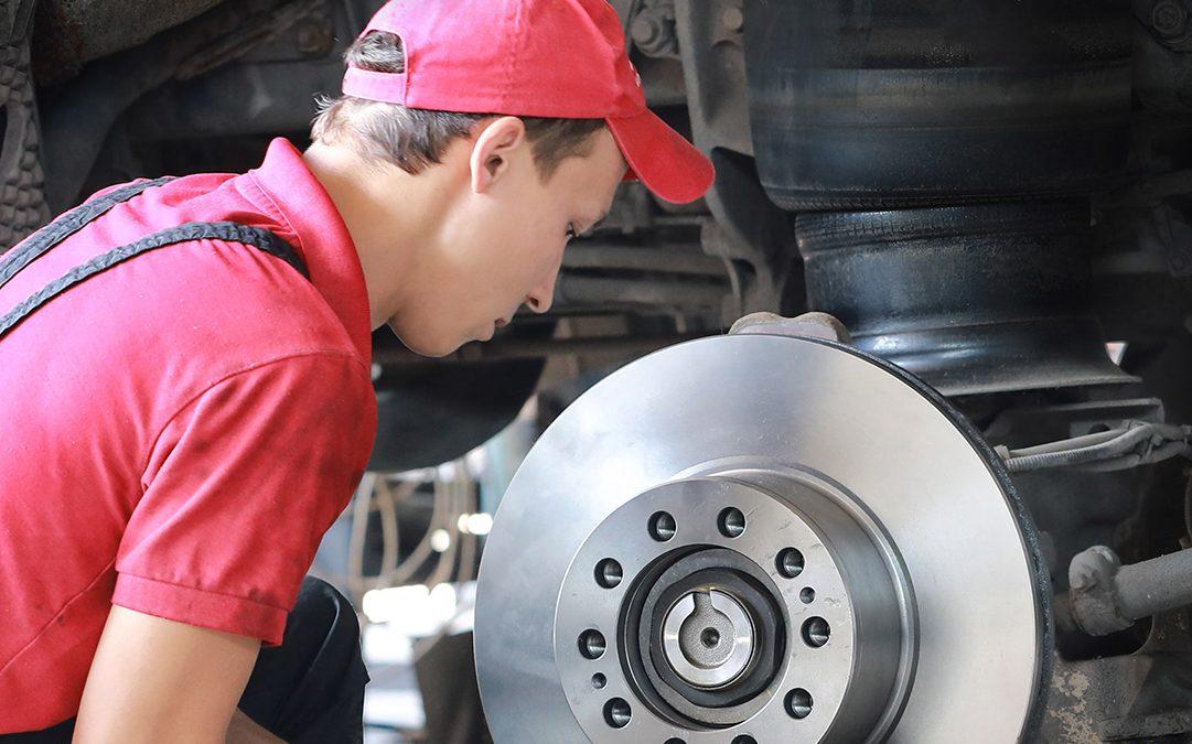 Un mécanicien répare un camion en remplaçant le disque de freinage.