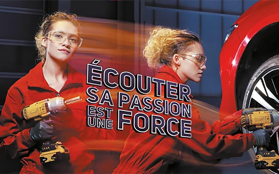 Image de promotion de la semaine des services de l'automobile 2021. Une jeune mécanicienne travaille sur la roue d'un véhicule rouge dans un atelier.