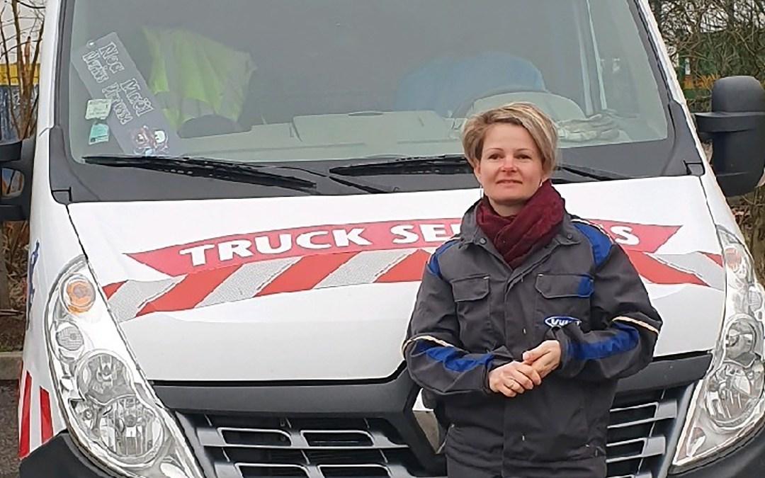 photo d'une femme mécanicienne en bleu de travail devant une camionnette