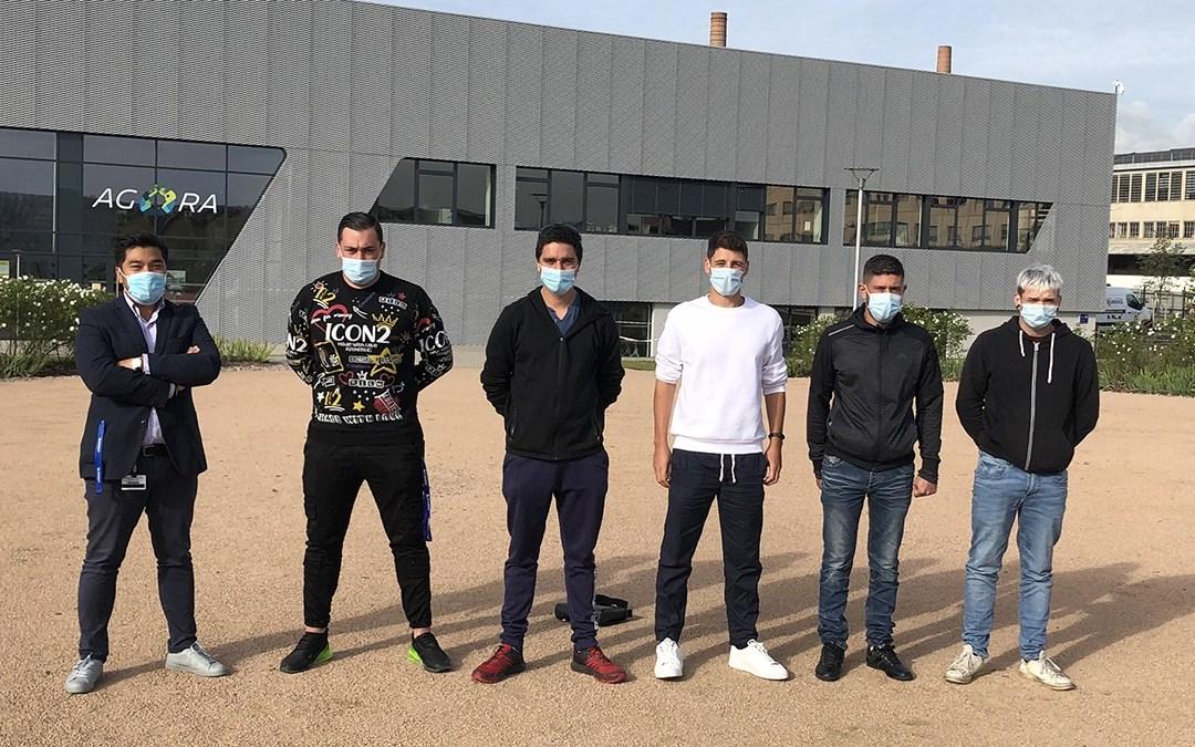 5 élèves et leur professeur se tiennent debout devant le batiment de leur formation